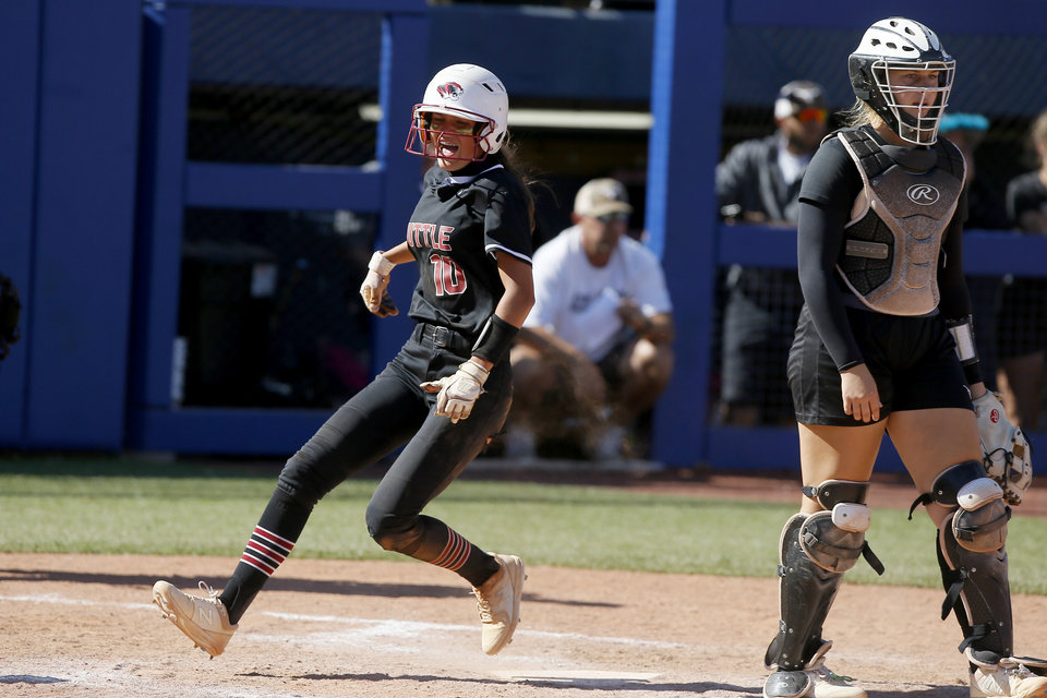 Photo - Tuttle's Olivia McBurnett celebrates as she score a run beside Lone Grove's Chloe Yeatts during the Class 4A state softball championship game between Tuttle and Lone Grove at USA Softball Hall of Fame Stadium in Oklahoma City, Saturday, Oct. 17, 2020. [Bryan Terry/The Oklahoman]