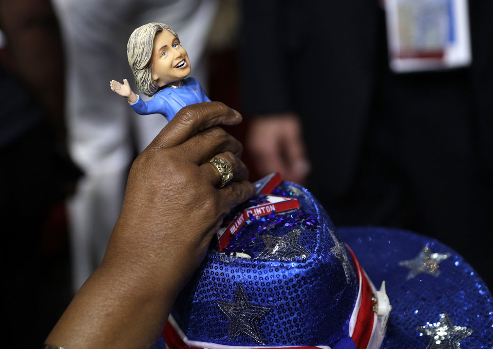 Photo - A delegate adjust a Hillary Clinton bubble-head doll on her head as she arrives at Wells Fargo Arena before the start of the second day session of the Democratic National Convention in Philadelphia, Tuesday, July 26, 2016. (AP Photo/John Locher)