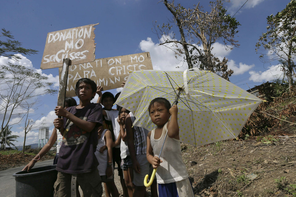 Residents affected by typhoon Bopha display messages begging for aid along a highway at Montevista township, Compostela Valley in southern Philippines Sunday Dec. 9, 2012. The number of missing in the wake of a typhoon that devastated parts of the southern Philippines has jumped to nearly 900 after families and fishing companies reported losing contact with more than 300 fishermen in the South China Sea and Pacific Ocean, officials said Sunday. (AP Photo/Bullit Marquez)