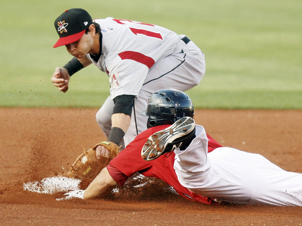 Photo - Albuquerque's Lance Zawadzki (12) tags out Oklahoma City's J.B. Shuck (4) as he slides into second base in the first inning during a minor league baseball game between the Oklahoma City RedHawks and the Albuquerque Isotopes at Chickasaw Bricktown Ballpark in Oklahoma City, Monday, April 23, 2012. Photo by Nate Billings, The Oklahoman