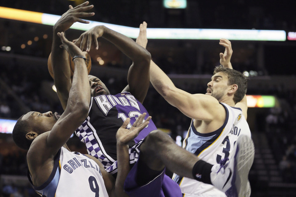 Photo - Sacramento Kings' Tyreke Evans (13) looses the ball between Memphis Grizzlies' Tony Allen (9), and Marc Gasol, right, during the first half of an NBA basketball game in Memphis, Tenn., Tuesday, Feb. 12, 2013. (AP Photo/Danny Johnston)