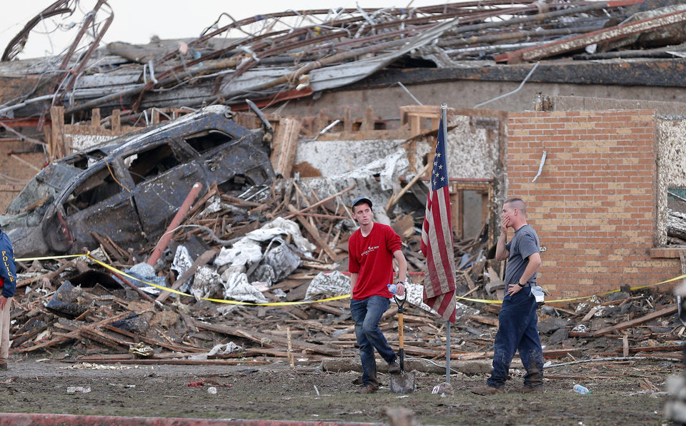 Two men stand in front of Plaza Towers Elementary School in Moore, Okla., after a tornado destroyed the school on Monday, May 20, 2013. Photo by Bryan Terry, The Oklahoman