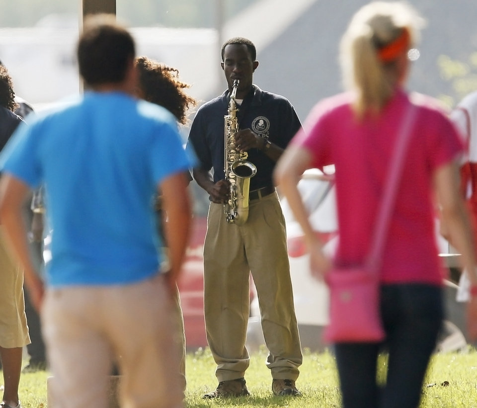 Photo - A saxophone player performs as people arrive before Oklahoma Strong: Coming Together in Faith, a memorial prayers service for the victims of recent Oklahoma tornadoes, at First Baptist Church in Moore Okla., Sunday, May 26, 2013. Photo by Nate Billings, The Oklahoman