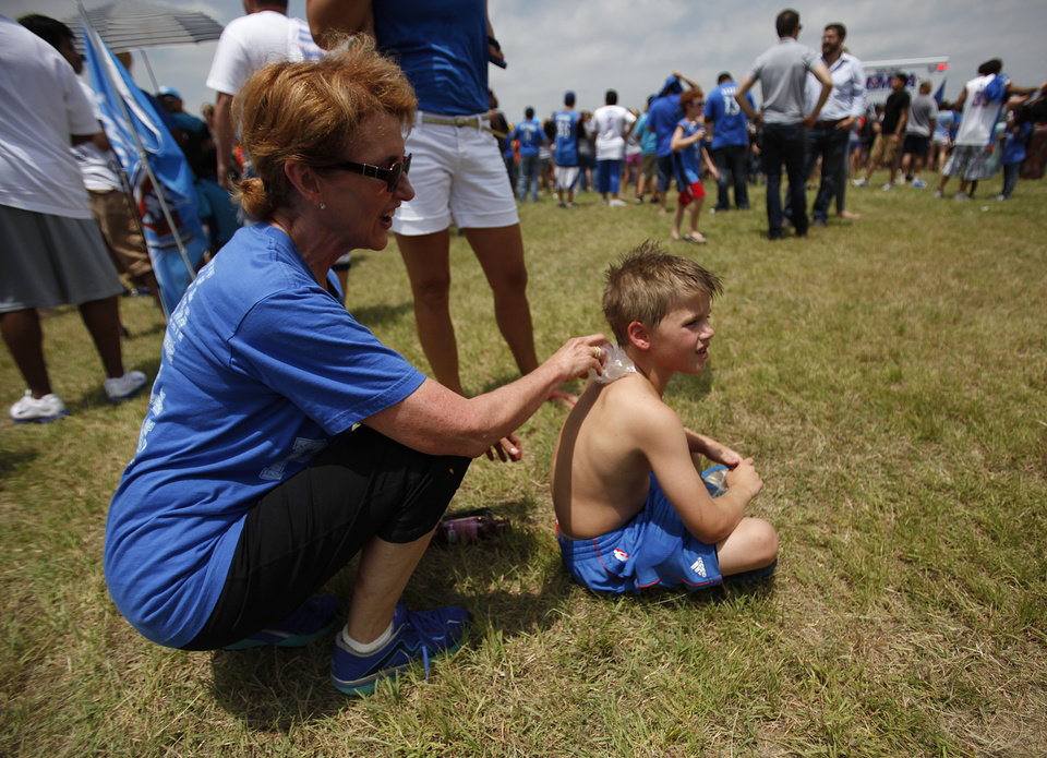 Photo - Debbie Pitman, of Oklahoma City, rubs ice on her grandson, Will Parker, 8, to cool him down during a welcome home rally for the Oklahoma City Thunder at a field near Will Rogers Airport in Oklahoma City, Friday, June 22, 2012.  Photo by Garett Fisbeck, The Oklahoman