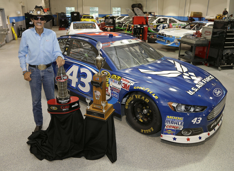 Photo - In this July 8, 2014 photo Richard Petty poses with two trophies at the race team's shop in Concord, N.C., Aric Almirola's trophy, left, for winning the Coke Zero 400 NASCAR auto race and his trophy, right, for winning the Firecracker 400 auto race 30 years ago. Almirola put the No. 43 car made famous by owner Richard Petty in Victory Lane for the first time in 544 races. (AP Photo/Chuck Burton)