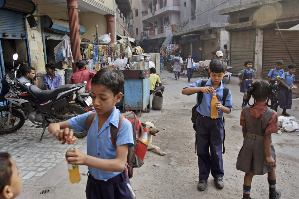 Indian schoolchildren make cold drinks as they walk to school in New Delhi, India, Tuesday, May 7, 2013. Northern and eastern plains continued to reel under the searing heat wave, with the mercury rising above 41 degrees Celsius (106 degrees Fahrenheit) in Delhi. (AP Photo/Tsering Topgyal)