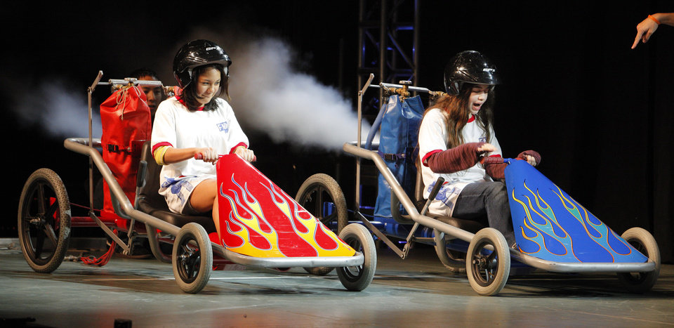 James Capps Middle School sixth-graders Valeria Poascencia and Laura Dees, both 12, race dragsters on stage during a  performance of FMA Live! at Kenneth Cooper Middle School in Oklahoma City Thursday, March 15, 2012. FMA Live! is a hip-hop science education program designed to inspire elementary and middle school students to pursue studies in science, technology, engineering, and math. Photo by Paul B. Southerland, The Oklahoman