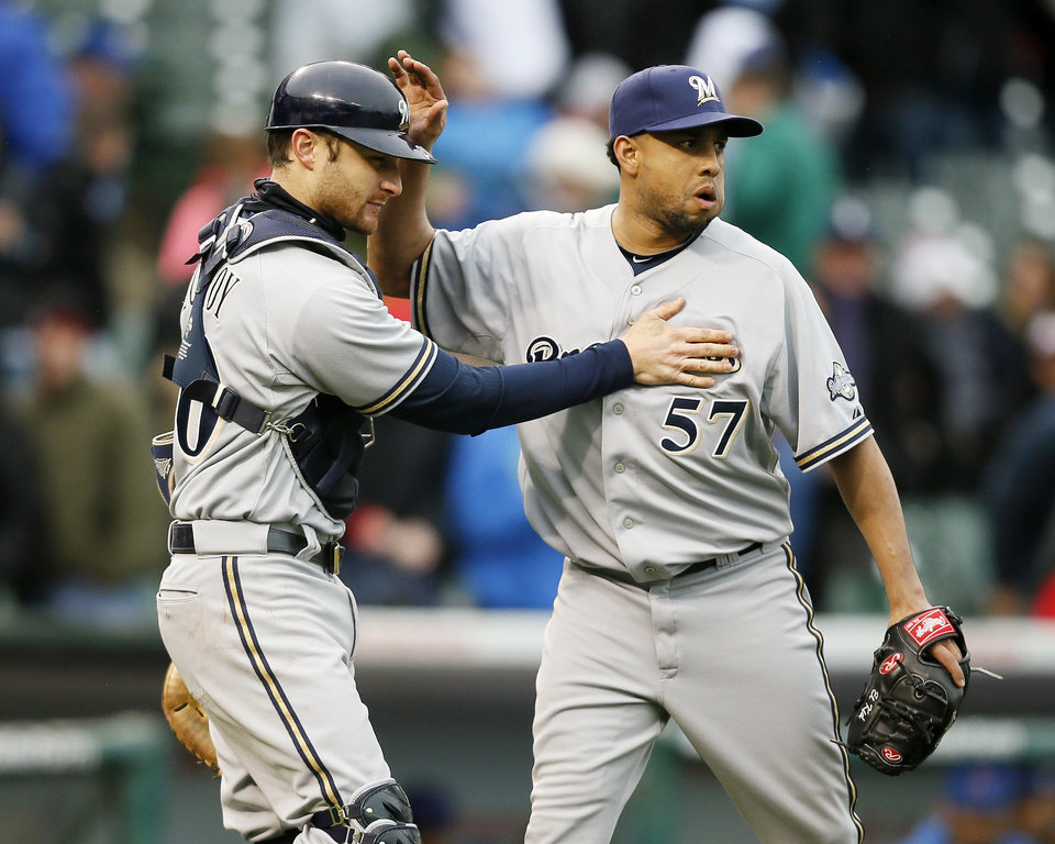 Photo - Milwaukee Brewers catcher Jonathan Lucroy, left, and relief pitcher Francisco Rodriguez, right, celebrate their victory against the Chicago Cubs in a baseball game on Friday, May 16, 2014, in Chicago. (AP Photo/Andrew A. Nelles)