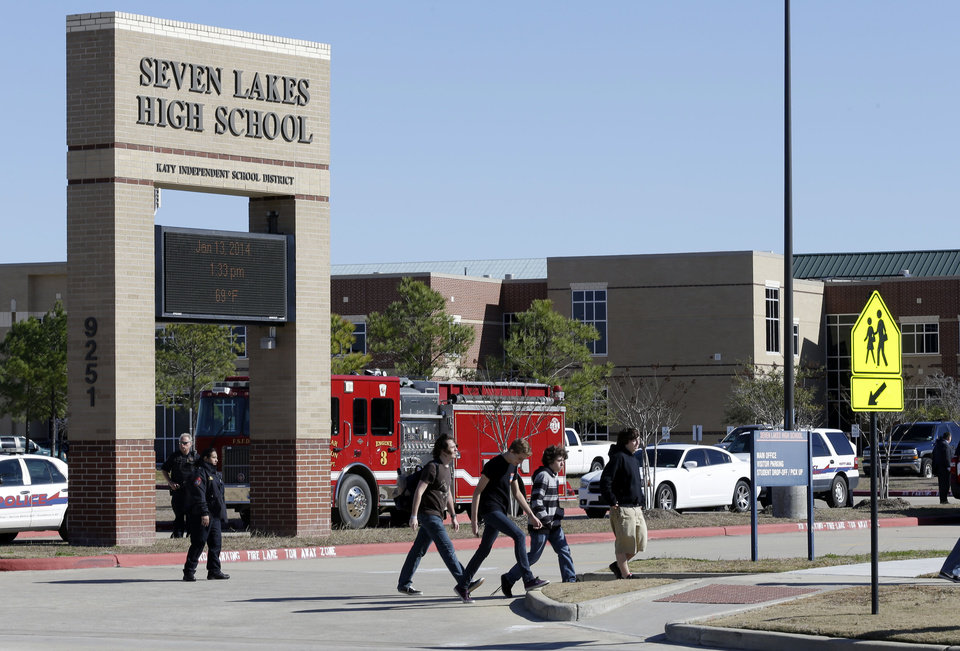 Photo - Students pass by Seven Lakes High School after being evacuated and  released from school for the day Monday, Jan. 13, 2014, in Katy, Texas. A bomb squad was called to the school after a potentially explosive device was found. (AP Photo/Pat Sullivan)