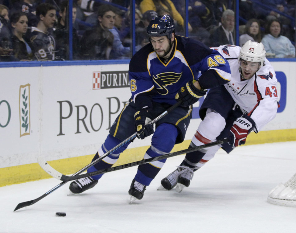 Photo - Washington Capitals' Tom Wilson (43) tries to poke the puck away from St. Louis Blues' Roman Polak (46) during the first period of an NHL hockey game, Tuesday, April 8, 2014, in St. Louis.(AP Photo/Tom Gannam)