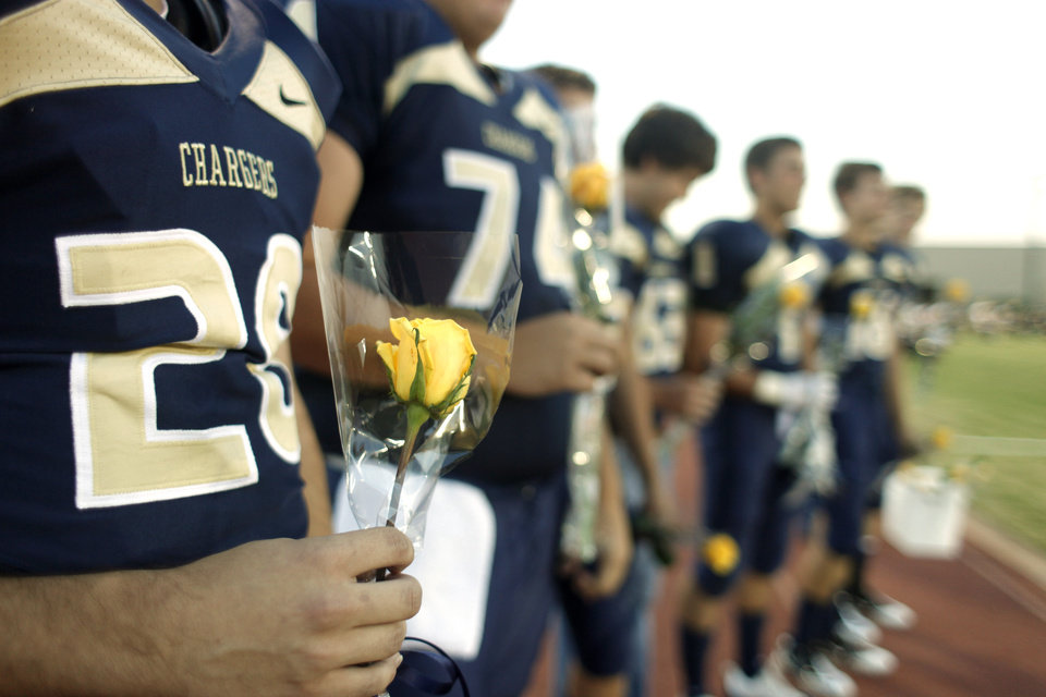 Photo - HH senior Sami Horani holds a rose to give to his mother during the pre-game ceremony for seniors during the high school football game between Heritage Hall and NOAH in Oklahoma City, Friday, Oct. 1, 2010. Photo by Doug Hoke, The Oklahoman.