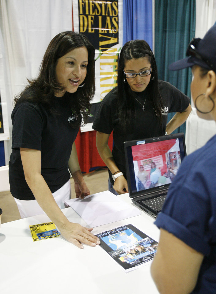 Brenda Hernandez (left) and Laura Adame speak to a fair goer about the Fiestas de Las Americas, during the Viva Oklahoma Hispanic Chamber Expo and Career Fair at the State Fair Park Transportation Building in Oklahoma City, OK, Saturday, July 25, 2009. By Paul Hellstern, The Oklahoman