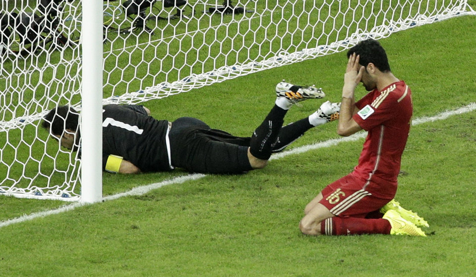 Photo - Spain's Sergio Busquets, right, holds his head after failing to score past Chile's goalkeeper Claudio Bravo during the group B World Cup soccer match between Spain and Chile at the Maracana Stadium in Rio de Janeiro, Brazil, Wednesday, June 18, 2014.  (AP Photo/Christophe Ena)