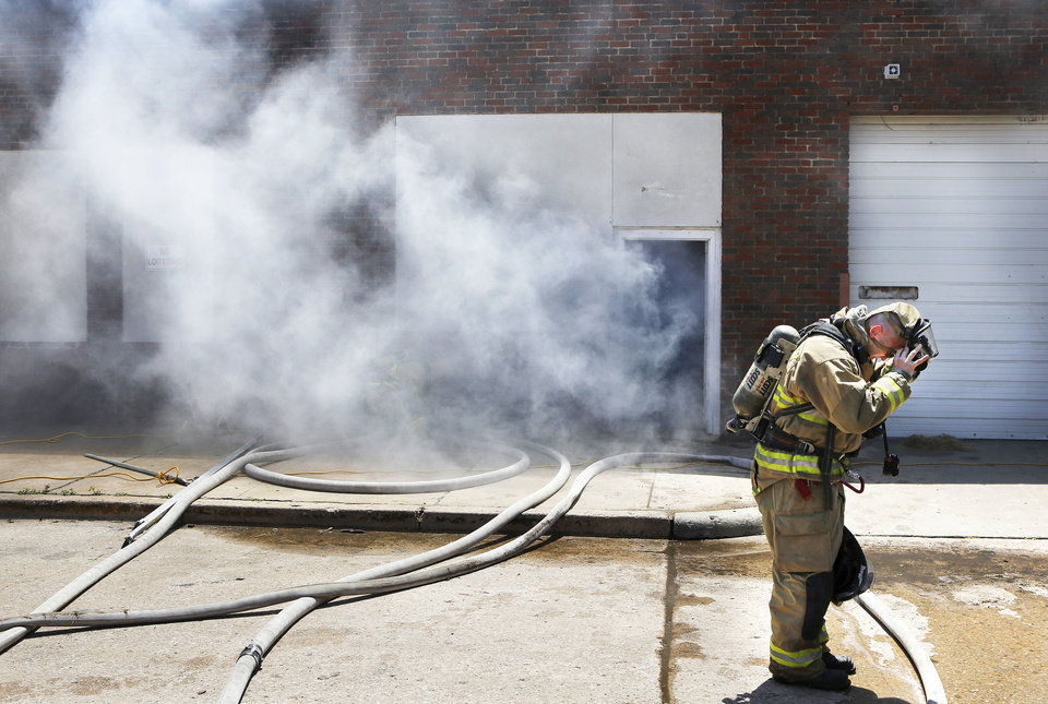 Photo - Smudge pots were lighted and topped with wet hay to fill this vacant building with dense smoke during a recent firefighter training session.Photos by Jim Beckel, THE OKLAHOMAN