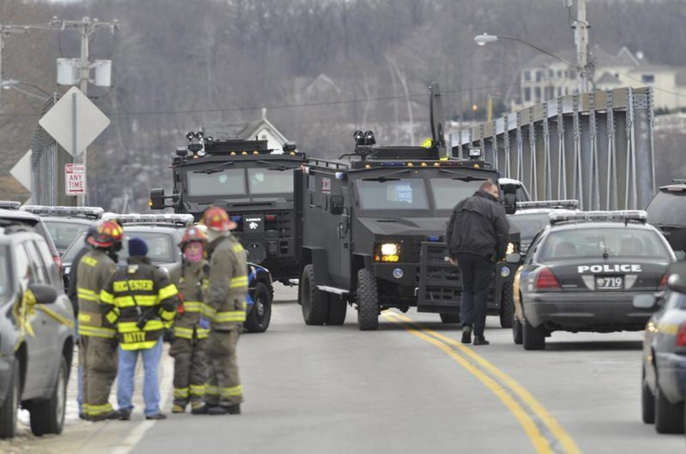 Photo - Swat teams appear at the scene of a fire in Webster, N.Y., Monday, Dec. 24, 2012. Police in New York state say a man who killed two firefighters in a Christmas Eve ambush had served 17 years for manslaughter in the death of his grandmother. (AP Photo/Messenger Post Media, Seth Binnix)