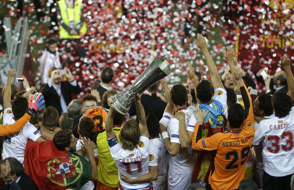 Photo - Sevilla players celebrate with the trophy after winning the Europa League soccer final between Sevilla and Benfica, at the Turin Juventus stadium in Turin, Italy, Wednesday, May 14, 2014. Sevilla beat Benfica 4-2 on penalties to win Europa League final. (AP Photo/Luca Bruno)
