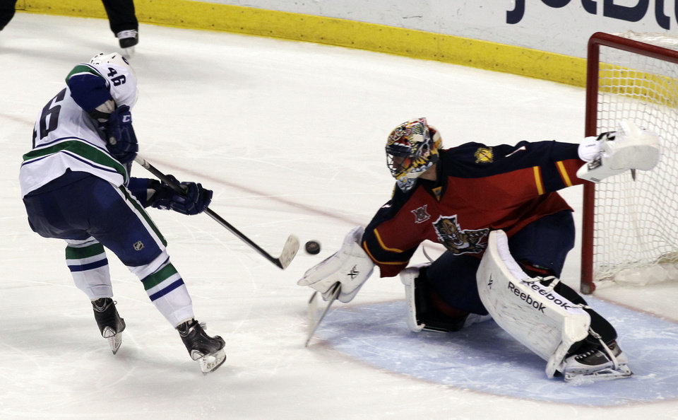 Photo - Vancouver Canucks'  Nicklas Jensen (46), of Denmark, scores the winning goal on Florida Panthers goalkeeper Roberto Luongo during a shootout of an NHL hockey game on Sunday, March 16, 2014, in Sunrise, Fla. The Canucks won 4-3 in a shootout. (AP Photo/Luis M. Alvarez)