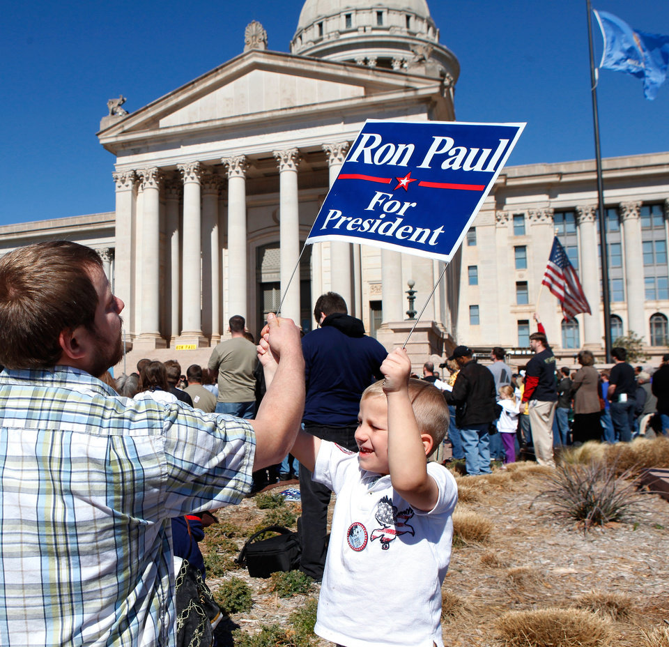 Photo - Noah Gosney, 5, gets help with his sign from his dad, James Gosney, who  brought Noah and his brother to the rally. They live in Stillwater. The elder Gosney said he's been very interested in Paul's campaign for about six months. About 1300 enthusiastic supporters rallied on the Capitol's south steps to hear and cheer comments by Republican presidential candidate Ron Paul during a brief visit to Oklahoma City on Saturday, Feb. 25, 2012. Photo by Jim Beckel, The Oklahoman