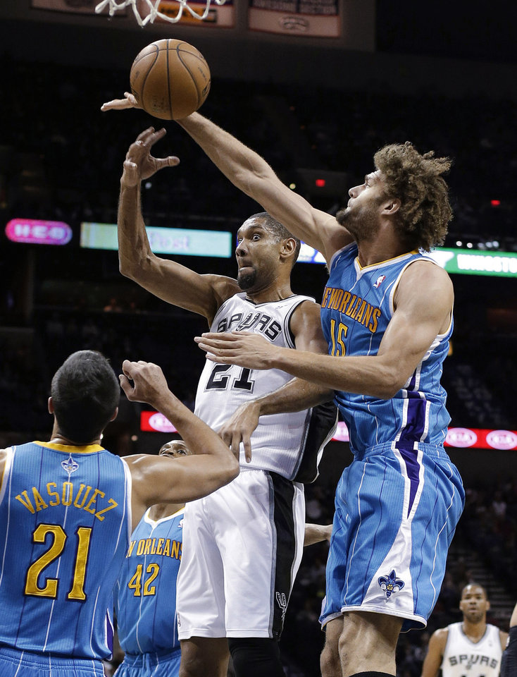 Photo - San Antonio Spurs' Tim Duncan (21) passes as New Orleans Hornets' Robin Lopez (15) and Greivis Vasquez (21) defend during the first quarter of an NBA basketball game, Friday, Dec. 21, 2012, in San Antonio. (AP Photo/Eric Gay)