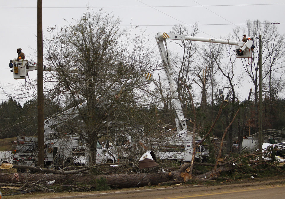 Power crews work on lines around storm debris in Monticello, Miss. on Wednesday, Dec. 26, 2012. More than 25 people were injured and at least 70 homes were damaged in Mississippi by the severe storms that pushed across the South on Christmas Day, authorities said Wednesday. (AP Photo/The Enterprise-Journal, Philip Hall)