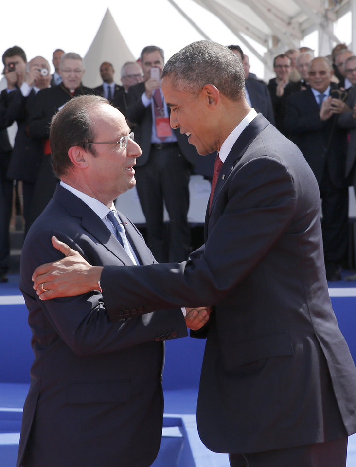 Photo - French President Francois Hollande, left, greets U.S. President Barack Obama during the D-Day commemoration at the Ouistreham beach, western France, Friday, June 6, 2014. World leaders and veterans gathered by the beaches of Normandy on Friday to mark the 70th anniversary of World War II D-Day landings. (AP Photo/Christophe Ena, Pool)