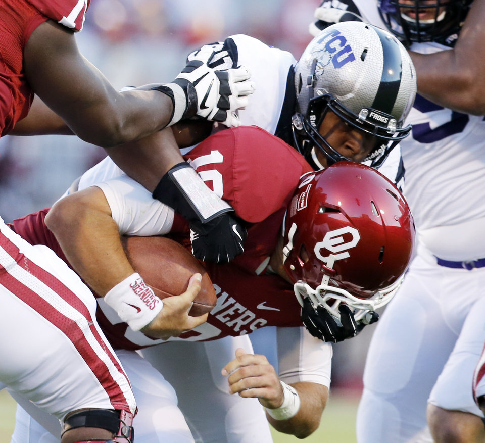 Photo - TCU's Terrell Lathan (90) sacks Oklahoma's Blake Bell (10) during a college football game between the University of Oklahoma Sooners (OU) and the TCU Horned Frogs at Gaylord Family-Oklahoma Memorial Stadium in Norman, Okla., on Saturday, Oct. 5, 2013. Photo by Steve Sisney, The Oklahoman