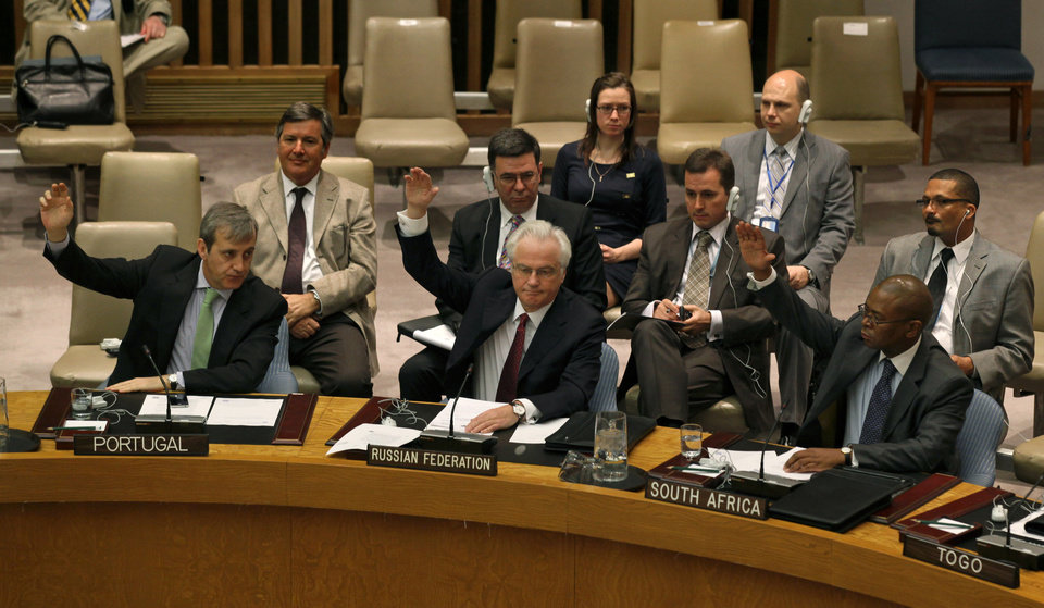 Photo -   Members of the United Nations Security Council, including Russia's U.N. Ambassador Vitaly Churkin, foreground second from left, raise their hands Saturday, April 14, 2012 at U.N. headquarters during a unanimous vote authorizing the deployment of the first wave of U.N. military observers to monitor a cease-fire between the Syrian government and opposition fighters. (AP Photo/Craig Ruttle)
