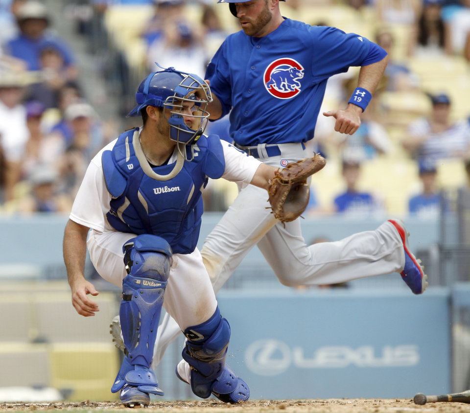 Photo - Chicago Cubs' Nate Schierholtz, right, beats the throw to Los Angeles Dodgers catcher Drew Butera, left, from center field, to score with Cubs' Chris Valaika on a single by the Cubs' Starlin Castro in the eighth inning of a baseball game on Sunday, Aug. 3, 2014, in Los Angeles. (AP Photo/Alex Gallardo)