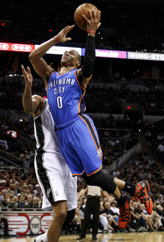 Photo - Oklahoma City's Russell Westbrook (0) goes past San Antonio's Tim Duncan (21)  during Game 2 of the Western Conference Finals in the NBA playoffs between the Oklahoma City Thunder and the San Antonio Spurs at the AT&T Center in San Antonio, Wednesday, May 21, 2014. Photo by Sarah Phipps, The Oklahoman