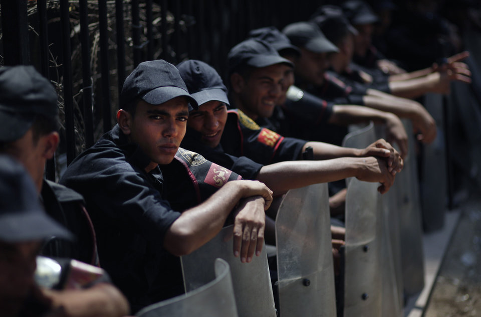 Egyptian riot police sit in the shade as they guard outside the parliament building in Cairo, Egypt, Tuesday, July 10, 2012. Egypt's Islamist-dominated parliament convened Tuesday in defiance of a ruling by the country's highest court and swiftly voted to seek a legal opinion on the decision that invalidated the chamber over apparent election irregularities. (AP Photo/Khalil Hamra) ORG XMIT: KH102