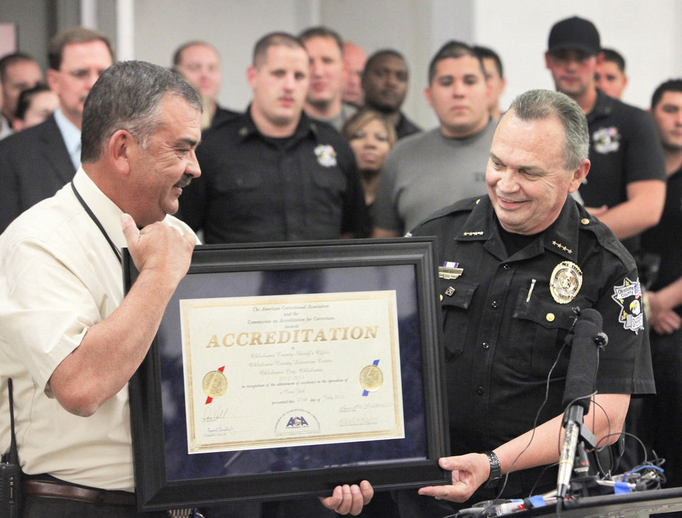 Photo - Jail Administrator Jack Herron recedes a certificate of accreditation from Oklahoma County Sheriff John Whetsel for the county jail facilities, Tuesday, September 11, 2012. Photo By David McDaniel/The Oklahoman  Jail Accreditation