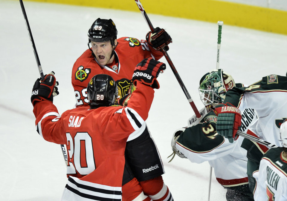 Photo - Chicago Blackhawks wingers Bryan Bickell (29) and Brandon Saad, left, celebrate after Bickell scored past Minnesota Wild goalie Niklas Backstrom of Finland, left, during the first period of an NHL hockey game, Tuesday, March 5, 2013 in Chicago.  (AP Photo/Brian Kersey)