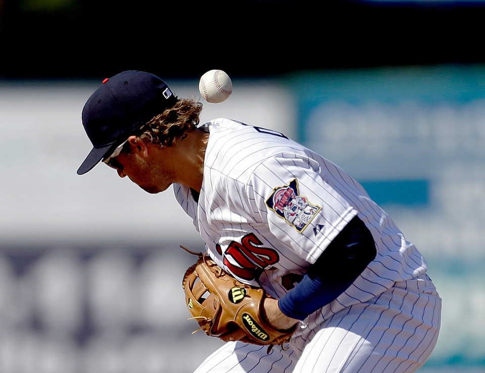 Photo - Minnesota Twins shortstop Brian Dozier loses the ball on a fielding error as Pittsburgh Pirates' Jeff Larish reaches first first base  in the ninth inning of a spring training exhibition baseball game, Sunday March 10, 2013, in Fort Myers, Fla. (AP Photo/David Goldman)