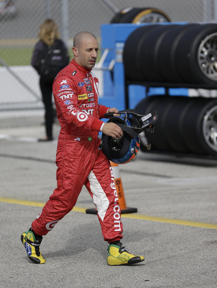Photo - Driver Tony Kanaan, of Brazil, walks back to his garage after a practice session for the IMSA Series Rolex 24 hour auto race at Daytona International Speedway in Daytona Beach, Fla., Thursday, Jan. 23, 2014.(AP Photo/John Raoux)