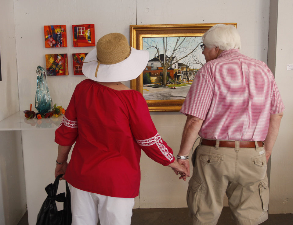 Photo - Doris Nelson and Ken Dobbins look at artwork in the South Hudson Gallery during opening day of the Festival of the Arts in downtown Oklahoma City TUesday, April 24, 2012. Photo by Doug Hoke, The Oklahoman
