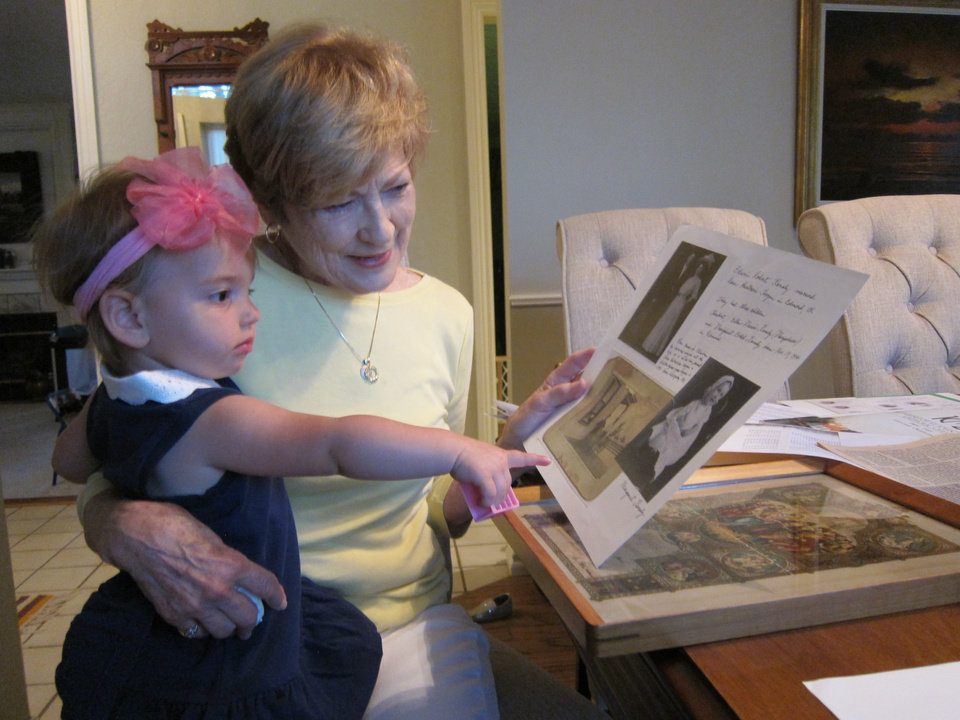 Photo - A member of a six-generation family of St. John the Baptist Catholic Church members, Kathleen O'Meara Marks shows her granddaughter Piper Price, 18 months, some family photos in her Edmond home.  Photo by Carla Hinton, The Oklahoman