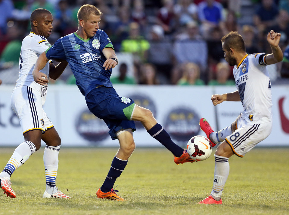 Photo - Oklahoma City's Nathan Polak (27), middle, tries to control the ball between LA's Andre Auras (63), left, and Dragan Stojkov (48) during a soccer game between the OKC Energy FC and LA Galaxy II at Pribil Stadium at Bishop McGuinness Catholic High School in Oklahoma City, Saturday, Aug. 16, 2014. Photo by Nate Billings, The Oklahoman