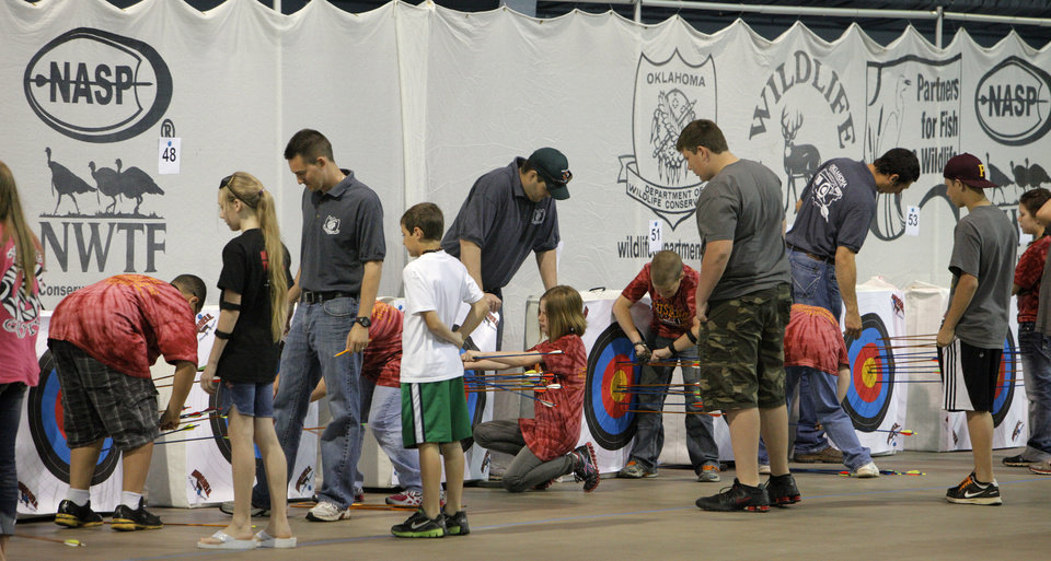 Photo - Students retrieve arrows after taking practice shots in the 10 meter during the Oklahoma's National Archery in the Schools Program State Shoot at State Fair Park in Oklahoma City Wednesday, March 28, 2012. Photo by Paul B. Southerland, The Oklahoman