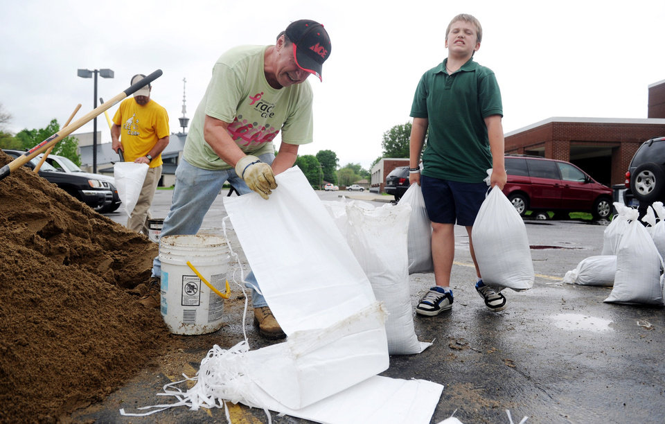 Photo - Tanner Adams, 11, right, struggles to move two heavy sandbags as David Gambrall,left, fills up more bags in the parking lot of Good Shepard Catholic School in Evansville, Ind. on Wednesday, April 26, 2011. Adams ,who is a fifth grader at Good Shepard, was dismissed from school, gave his mother his backpack and asked to help in the volunteer efforts. Adams does not have flood waters at his house but wanted to do something to help those who are affected by the heavy rains and rising waters. (AP Photo/The Evansville Courier & Press, Erin McCracken)