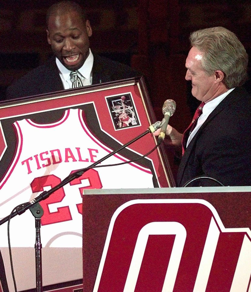 Photo - Oklahoma Athletic Director Steve Owens, right, gives Wayman Tisdale, the former Oklahoma great basketball player, his jersey during half time activities Saturday, Feb. 22, 1997, in Norman, Okla. Tisdale's jersey is the first to be retired in the University of Oklahoma's history. (AP Photo/J. Pat Carter)