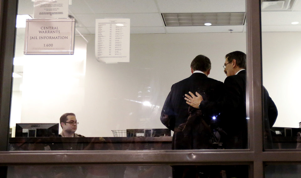 Photo - Texas Gov. Rick Perry, center, is booked at the Blackwell Thurman Criminal Justice Center, Tuesday, Aug. 19, 2014, in Austin, Texas. Perry has been booked on two felony counts of abuse of power for carrying out a threat to veto funding to state public corruption prosecutors. (AP Photo/Eric Gay)