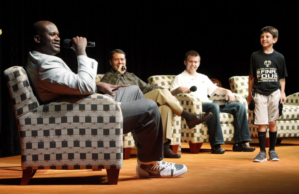 Photo - Former NBA star Shaquille O'Neal sits beside with Oklahoma State basketball coach Travis Ford and OSU basketball player Keiton Page as Travis Ford's son Shane greets the group during a question and answer session at Gallagher-Iba Arena on the campus of Oklahoma State University in Stillwater, Okla., Tuesday, April 3, 2012. Oklahoma State University's Student Government Association Speakers Board hosted the event. Photo by Bryan Terry, The Oklahoman