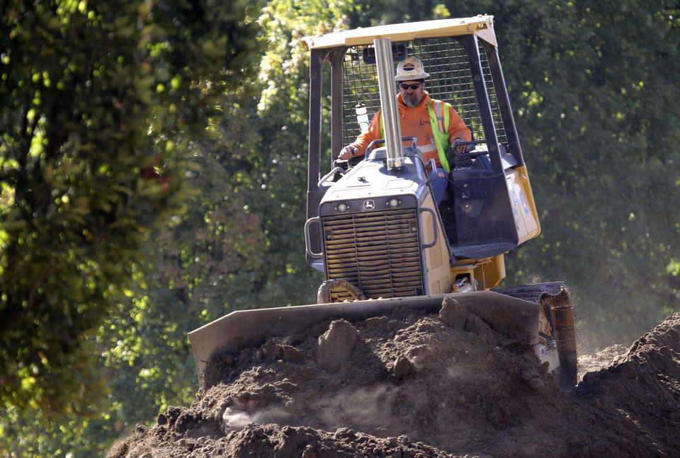 Photo - A worker levels dirt for a light rail bridge construction project over the Willamette River in Portland, Ore., Friday.  The Labor Department reported Friday that the unemployment rate fell to 7.8 percent in September, a decline of 0.3 percentage point and the lowest since January 2009. The government said the economy created 114,000 jobs, about as expected, and generated 86,000 more jobs in July and August than first estimated. AP PHOTO  Don Ryan - AP