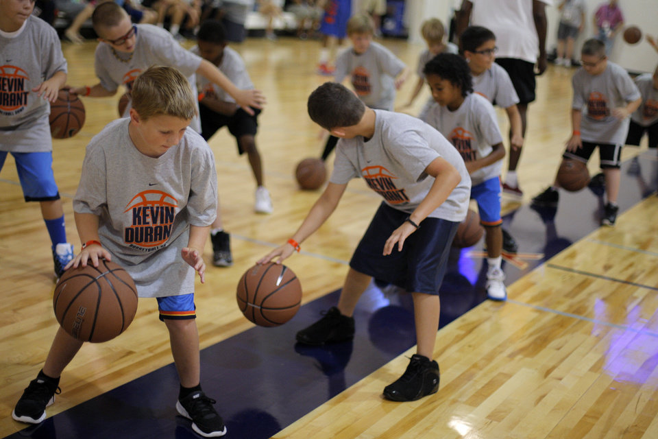 Photo - Children participate in dribbling drills during the Kevin Durant basketball camp at Heritage Hall Wednesday, June 29, 2011.  Photo by Garett Fisbeck, The Oklahoman