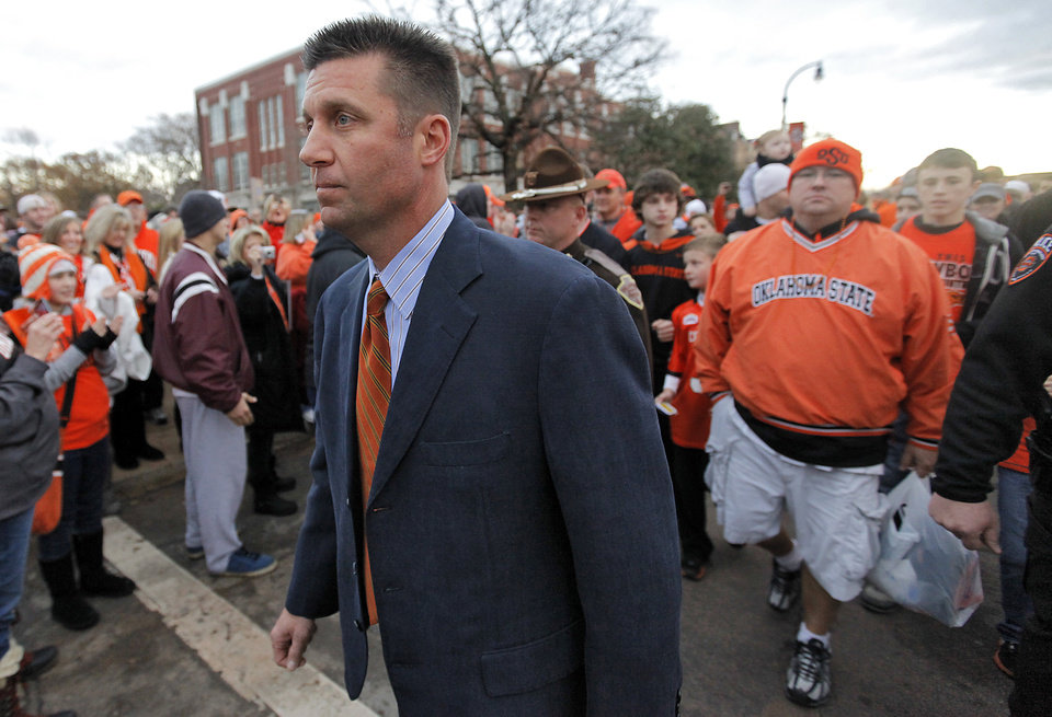 Photo - Coach Mike Gundy is followed by fans as he takes part in the 'Spirit Walk' before the Bedlam college football game between the Oklahoma State University Cowboys (OSU) and the University of Oklahoma Sooners (OU) at Boone Pickens Stadium in Stillwater, Okla., Saturday, Dec. 3, 2011. Photo by Chris Landsberger, The Oklahoman