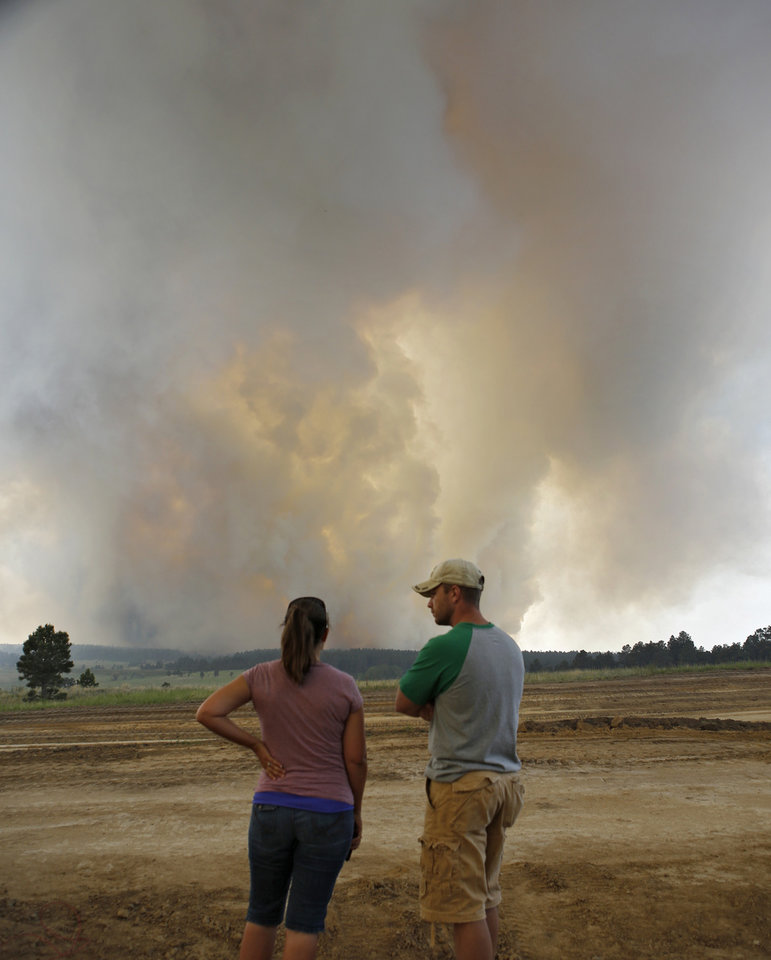 Photo - Shad and Melisa Dohl watch as fire crowns in the trees on a wildfire in the Black Forest area north of Colorado Springs, Colo., on Wednesday, June 12, 2013. The number of houses destroyed by a wildfire near Colorado Springs could grow to around 100, and authorities fear it's possible that some people who stayed behind might have died.  (AP Photo/Ed Andrieski)