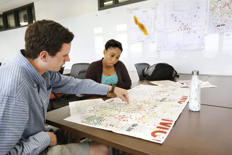 Photo -  OU students Andrew Oakes and Zaharaou Sylla, both seniors majoring in petroleum engineering, discuss data on geological maps they are consulting in the new Ronnie Irani Center for Energy Solutions on the 14th floor of the Sarkey's Energy Center on the University of Oklahoma campus. [Photo by Jim Beckel, The Oklahoman]