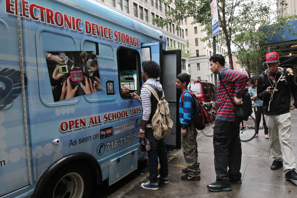 In this Sept. 27, 2012 photo, students from New York\'s Washington Irving educational complex line up to leave their cellphones and other electronic devices, for a dollar a day per item, in a privately operated truck parked near their school. Cellphones are banned in all New York City public schools, but the rule is widely ignored except in schools with metal detectors. Outside those schools, entrepreneurs park trucks where students drop off devices before class and get them back at the end of the day.(AP Photo/Tina Fineberg)