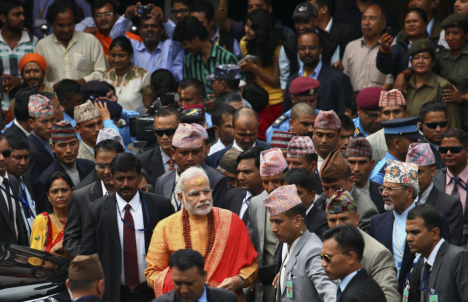 Photo - Indian Prime Minister Narendra Modi, foreground in saffron clothing, leaves after his visit at the Pashupatinath Temple in Katmandu, Nepal, Monday, Aug. 4, 2014. Modi flew to the neighboring Himalayan nation Sunday to meet top leaders, offer prayers at a revered Hindu temple and address the parliament. (AP Photo/Kiran Panday)