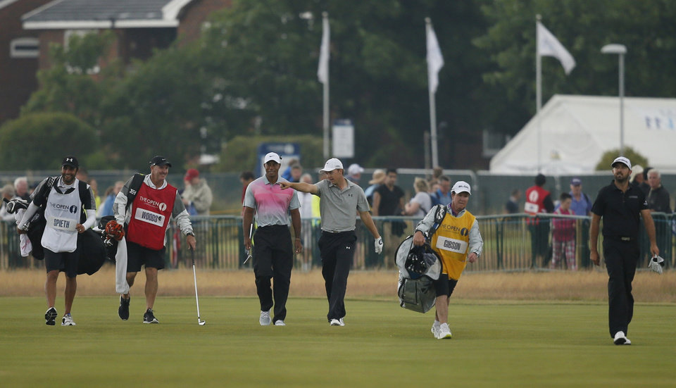 Photo - Tiger Woods of the US, center left, walks along the 18th fairway with Jordan Spieth of the US, center right, and Rhein Gibson of Australia, right, during the third day of the British Open Golf championship at the Royal Liverpool golf club, Hoylake, England, Saturday July 19, 2014. (AP Photo/Alastair Grant)